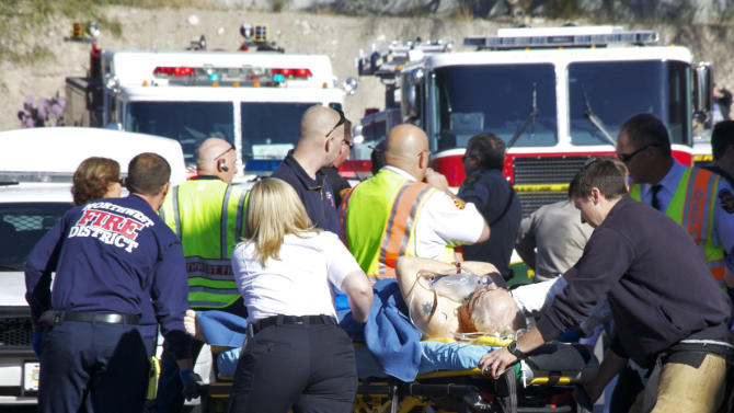 Emergency personnel attend to a shooting victim  outside a shopping center in Tucson, Ariz. on Saturday, Jan. 8, 2011 where U.S. Rep. Gabrielle Giffords, D-Ariz., and others were shot as the congresswoman was meeting with constituents.  (AP Photo/James Palka)