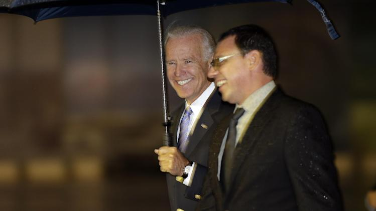 Vice President Joe Biden, holding an umbrella, walks with an unidentified Mexican official upon his arrival at the airport in Mexico City, Mexico, Thursday, Sept. 19, 2013. Biden will meet with Mexico's President Enrique Pena Nieto during his one-day visit. (AP Photo/Dario Lopez-Mills)
