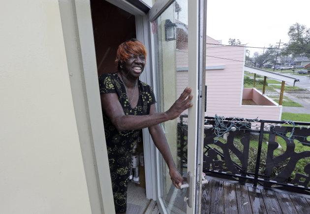 In this Wednesday, Aug. 29, 2012 photo, Melba Leggett-Barnes pulls the door of her Lower 9th Ward home from blowing open as Hurricane Isaac hits New Orleans. (AP Photo/David J. Phillip)