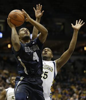Georgetown's D'Vauntes Smith-Rivera (4) drives against Marquette's Steve Taylor Jr., right, during the second half of an NCAA college basketball game on Thursday, Feb. 27, 2014, in Milwaukee