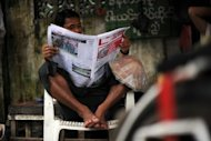 "A man reads a local journal in Yangon in August. Myanmar's state newspapers signalled a historic change in focus on Saturday, announcing a plan to transform into ""public service media"""