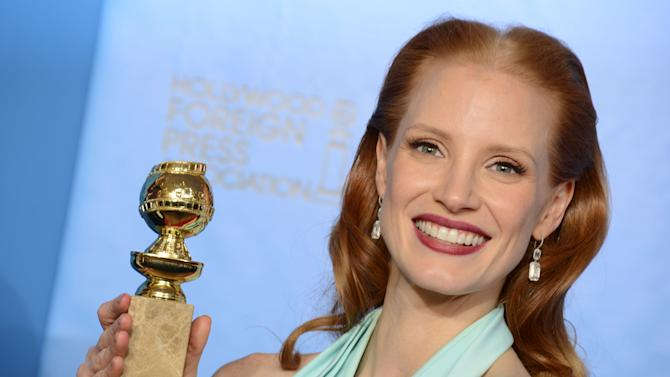 """Actress Jessica Chastain poses with the award for best performance by an actress in a motion picture - drama for """"Zero Dark Thirty"""" backstage at the 70th Annual Golden Globe Awards at the Beverly Hilton Hotel on Sunday Jan. 13, 2013, in Beverly Hills, Calif. (Photo by Jordan Strauss/Invision/AP)"""