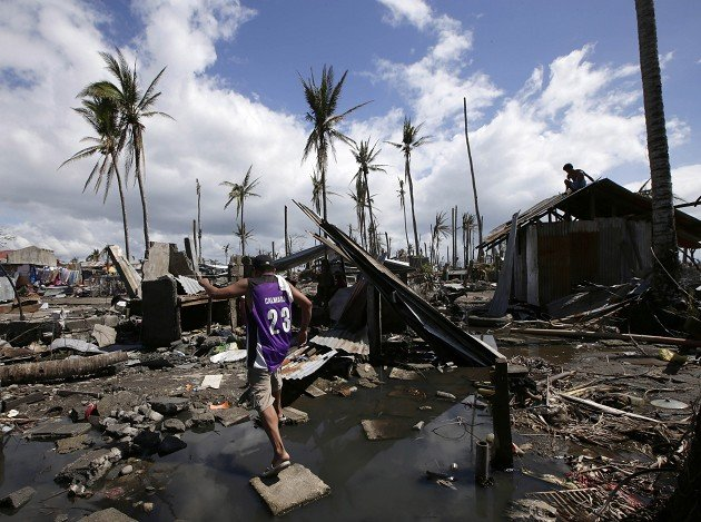 Typhoon survivor John Sarenio revisits his home at Tacloban city, Leyte province in central Philippines (AP)
