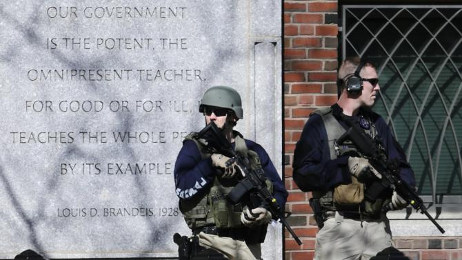 FILE - U.S. Marshals in tactical gear stand guard outside Boston's Moakley Federal Court House after if was evacuated, Wednesday, April 17, 2013. The building was evacuated amid conflicting reports that a suspect in the Boston Marathon bombing was in custody. (AP Photo/Charles Krupa)