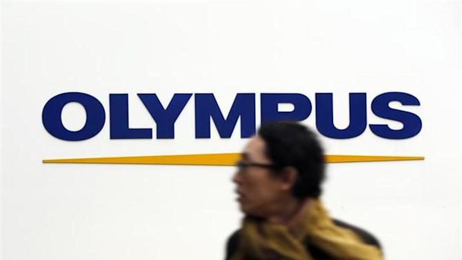 A man passes a logo of Olympus Corp outside the company's showroom in Tokyo December 21, 2012. REUTERS/Yuriko Nakao/Files