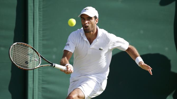 Pablo Andujar of Spain hits a shot during his match against Tomas Berdych of the Czech Republic at the Wimbledon Tennis Championships in London