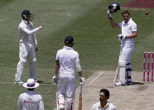 England's Ballance indicates he needs a new helmet after being hit by a delivery from Australia's Johnson during the second day of the fifth Ashes cricket test at the Sydney cricket ground