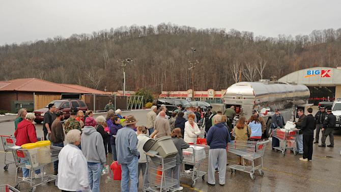West Virginia State Troopers fill water jugs at the Kmart in Elkview, W.Va., Friday, Jan. 10, 2014. Emergency crews are setting up water depots at many locations around the state following a chemical spill Thursday on the Elk River that compromised the public water supply to nine counties. (AP Photo/Tyler Evert)