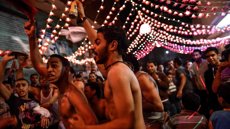 In this Tuesday, April 16, 2013 photo, shirtless young Egyptian men dance at a wedding party in Cairo, Egypt. Egypt's economy has been hard hit by the two years of turmoil that followed the ouster of longtime President Hosni Mubarak. Half of the country's 85 million people live at or below the poverty line of $2 a day and rely on government subsidies of wheat and fuel for survival.(AP Photo/Eman Helal)