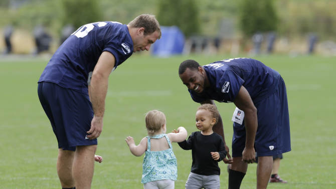 Seattle Seahawks wide receiver Percy Harvin, right, laughs as his son Jaden, 1, second from right, interacts with Kaydence Miller, 1, the daughter of Seahawks tight end Zach Miller, left, following the final day of NFL football training camp, Wednesday, Aug. 13, 2014, in Renton, Wash. (AP Photo/Ted S. Warren)
