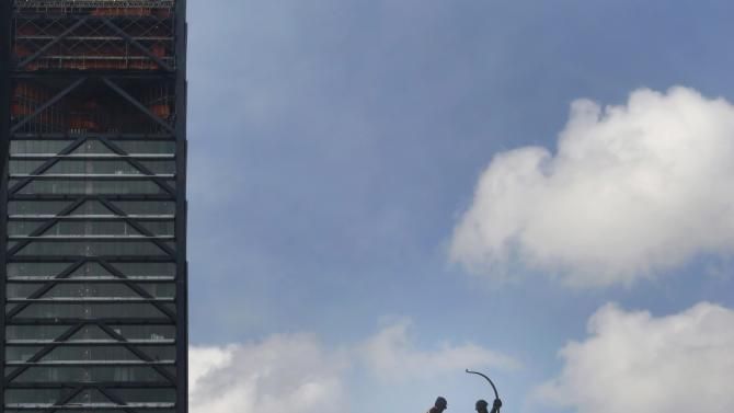 Two workers stand on scaffolding as they clean the Diana la Cazadora monument on Reforma Avenue in Mexico City