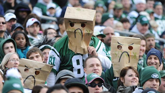Specatators use bags over their heads while watching the first half of an NFL football game between the New York Jets and the Arizona Cardinals, Sunday, Dec. 2, 2012, in East Rutherford, N.J. (AP Photo/Bill Kostroun)