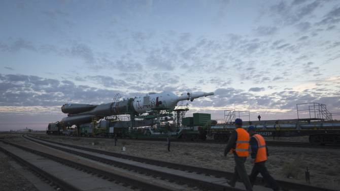 Railway workers walk in front of the Soyuz TMA-14M spacecraft as it is transported to its launch pad at Baikonur cosmodrome