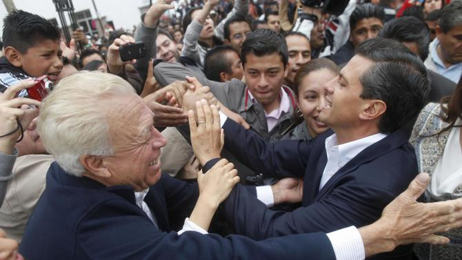 Enrique Pena Nieto, right, presidential candidate for the Revolutionary Institutional Party (PRI) right, greets supporters after casting his vote during general elections in Atlacomulco, Mexico, Sunday, July 1, 2012. According to polls, the PRI, holds a sizeable lead in these elections, after being kicked out of the top office by voters 12 years ago. (AP Photo/Esteban Felix)