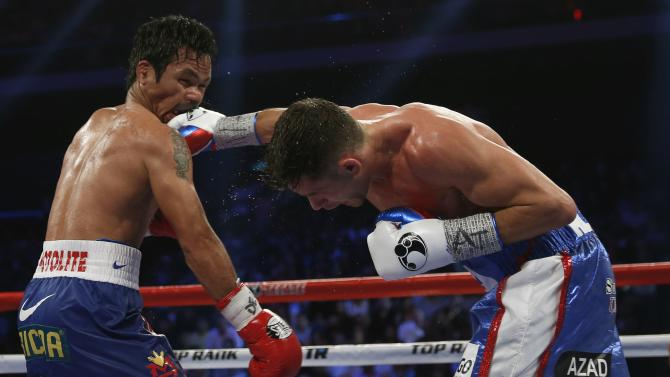 Pacquiao of the Philippines takes a punch from Algieri of the U.S. during their WBO 12-round welterweight title fight in Macau
