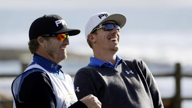 Hunter Mahan, right, laughs with caddie John Wood after hitting from the 18th tee of the Pebble Beach Golf Links during the first round of the AT&T Pebble Beach Pro-Am golf tournament, Thursday, Feb. 7, 2013, in Pebble Beach, Calif. (AP Photo/Eric Risberg)
