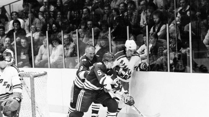 FILE-This Oct. 29, 1979 file photo shows Gordie Howe (9) of the Hartford Whalers and his son and teammate Mark Howe (5) taking the puck from New York Rangers' Ron Greschner (4) in first period action at Madison Garden in New York City.  Mark Howe has earned the right to join his father, Gordie, in the Hockey Hall of Fame. Howe will be inducted Monday Nov. 14, 2011 in Toronto with Ed Belfour, in his first year eligibility, Doug Gilmour and Joe Nieuwendyk. (AP Photo/File)