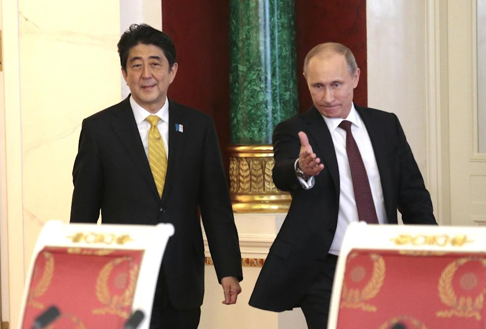 Russian President Vladimir Putin, right, and visiting Japanese Prime Minister Shinzo Abe walk in a hall to take part in a final news conference in Moscow's Kremlin, Monday, April 29, 2013. Abe is in Russia on an official visit. (AP Photo/Ivan Sekretarev, pool))