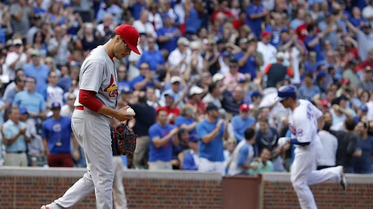 St. Louis Cardinals starting pitcher Joe Kelly, left, returns to the mound after giving up a three-run home run to Chicago Cubs' Ryan Sweeney, right, during the second inning of a baseball game Friday, July 25, 2014, in Chicago. Welington Castillo and Luis Valbuena also scored on the play. (AP Photo/Charles Rex Arbogast)
