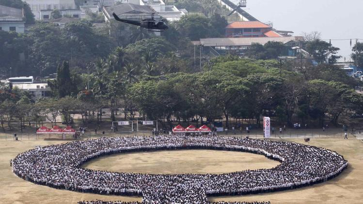 A helicopter hovers over a female symbol formed by people, as part of celebrations for International Woman's Day in Manila