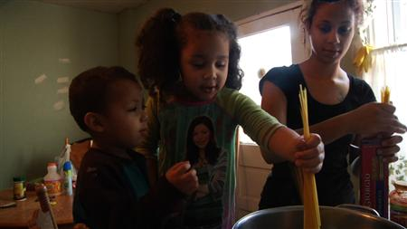 Barbie Izquierdo and her two children cook dinner in the film &quot;A Place at the Table&quot; in this undated publicity handout photo courtesy of Magnolia Pictures. REUTERS/Magnolia Pictures/Handout