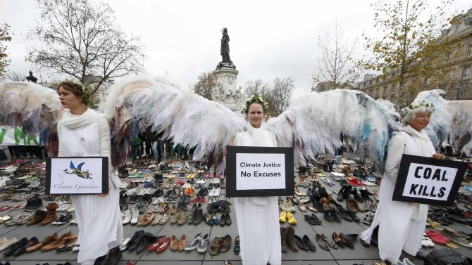 Environmental activists stand among pairs of shoes symbolically placed on the Place de la Republique ahead of the World Climate Change Conference 2015 in Paris