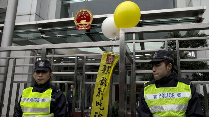 """Policemen stand near a portrait of jailed Chinese Nobel Peace Prize laureate Liu Xiaobo with balloons and slogans reading """"Release Liu Xiaobo"""", during a protest urging for his release, outside the Chinese liaison office in Hong Kong"""
