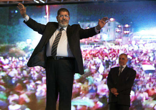 FILE - In this Sunday, May 20, 2012 file photo, the Muslim Brotherhood's presidential candidate Mohammed Morsi hold a rally in Cairo, Egypt. A statement on the Egyptian president's office's Twitter ac
