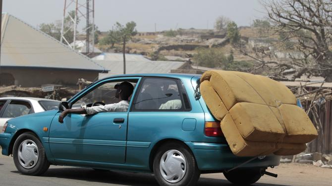 A mattress is seen strapped to the back of a car as people flee the violence from Boko Haram, in Adamawa the north east of Nigeria
