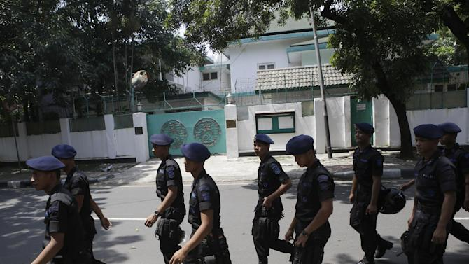 In this Friday, May 3, 2013, police officers are deployed outside the embassy of Myanmar to anticipate a planned Muslim hardliner protest and to provide extra security for after the police revealed a plot of a terror attack on the premise on the Facebook page of a suspected militant, in Jakarta, Indonesia. The use of social networking to groom potential attackers is posing a new challenge to authorities in the world's most populous Muslim country that has been struggling to eradicate militant groups. (AP Photo/Dita Alangkara)
