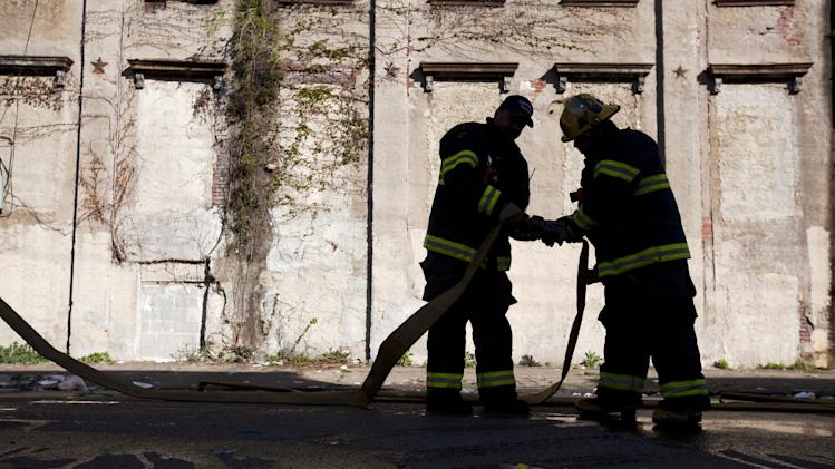 Firefighters pack up equipment in the aftermath of a fire in a warehouse on York Street near Kensington Avenue in Philadelphia on Monday, April 9, 2012. Two firefighters died after a wall collapsed on them while they fought the massive early-morning blaze. (AP Photo/Matt Rourke)