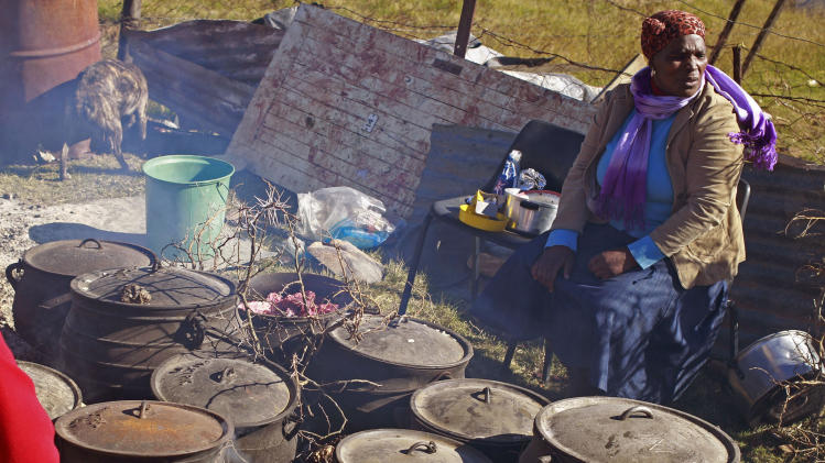 A woman prepares food in cast iron pots for mourners who were attending the funeral of Florence Mandela, a relative of former president Nelson Mandela, in Qunu, in the Eastern Cape Province, South Africa, Saturday,  June 15, 2013.  In Pretoria, South Africa, Nelson Mandela spent an eighth day in hospital where he is being treated for a recurring lung infection. (AP Photo/Schalk van Zuydam)