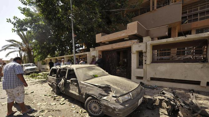 People look at a damaged car outside the Swedish consulate after a car bomb explosion, in Benghazi