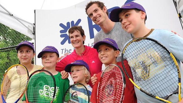 British tennis player Andy Murray (2nd R) and his mother Judy (C), a tennis coach, pose with children after giving lessons to young tennis players (AFP)