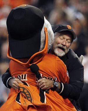FILE - In this file photo from Thursday, Oct. 7, 2010, actor Robin Williams hugs San Francisco Giants mascot Lou Seal during the first inning of Game 1 of baseball's National League Division Series in San Francisco. Williams was everywhere in San Francisco, it seemed, as he made a place for himself in the everyday fabric of a city where he once said he passed for normal. (AP Photo/Ben Margot, File)