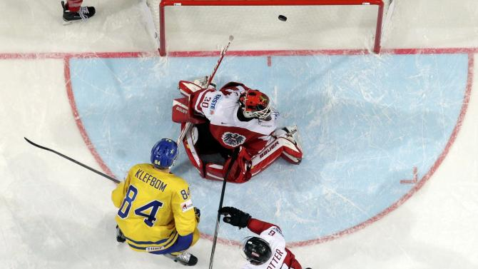 Sweden's Klefbom scores a goal past Austria's goaltender Swette and Rotter during their Ice Hockey World Championship game at the O2 arena in Prague