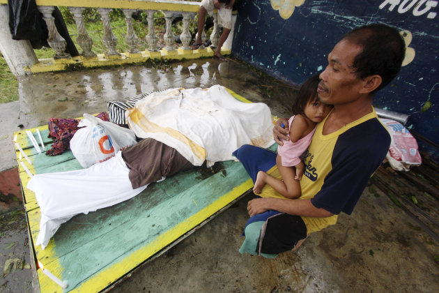 A resident cuddles his child next to the bodies of three children who were killed in a landslide that swept their home after Typhoon Bopha made a landfall in Compostela Valley in southeastern Philippi