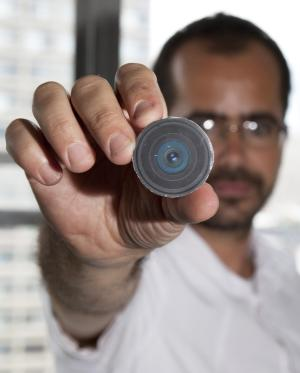 "This Aug. 24, 2010 photo provided by New York University arts professor Wafaa Bilal, shows Bilal holding the prototype of a digital camera that he had implanted in the back of his head, in New York.  Bilal, a visual artist widely recognized for his interactive and performance pieces, has undergone surgery to implant a tiny camera in the back of his head for an artwork commissioned by a new museum in Doha, Qatar. Titled ""The 3rd I,"" it is one of 23 contemporary works commissioned for the opening of Mathaf: Arab Museum of Modern Art on Dec. 30, 2010. (AP Photo/Wafaa Bila, Bard Farwell) NO SALES"