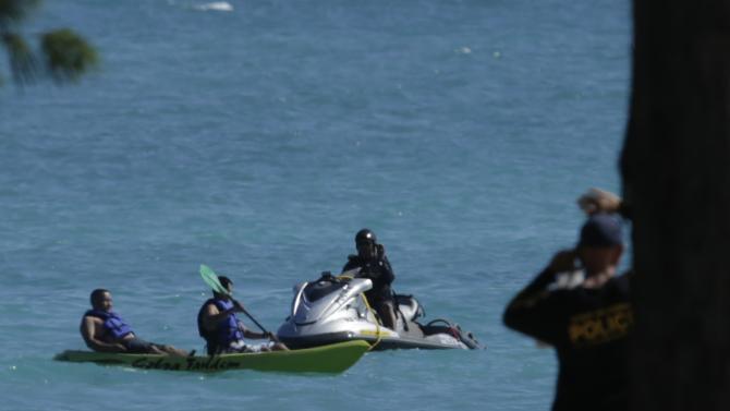 A police jet ski moves kayakers away from nearby Pacific Ocean waters where U.S. President Barack Obama and his party are swimming at Bellows Air Force Station Beach, Hawaii