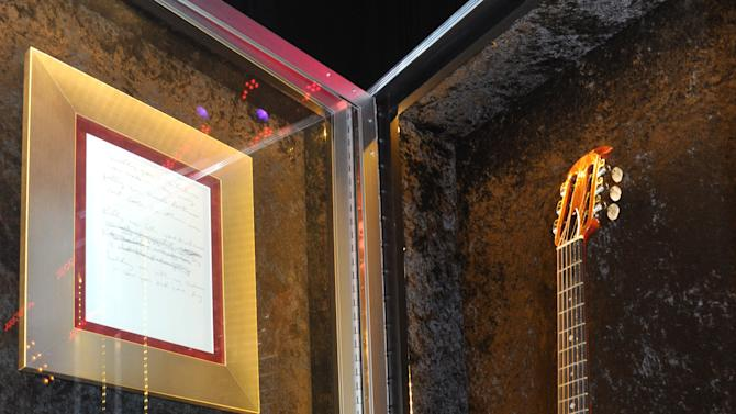 """A Nirvana Ovation acoustic guitar played by Kurt Cobain is displayed at the launch of Hard Rock International's traveling music memorabilia collection, """"Gone Too Soon,"""" Wednesday, Feb. 13, 2013, at Hard Rock Cafe New York.   """"Gone Too Soon"""" pays tribute to music icons whose lives and career where tragically cut short and will be on tour at Hard Rock locations in the U.S. throughout 2013. (Photo by Diane Bondareff/Invision for Hard Rock International/AP Images)"""