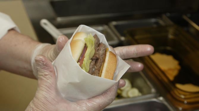 In this Sept. 15, 2011 photo, Liz Shires, Wendy's research and development laboratory coordinator, wraps a finished Dave's Hot 'N Juicy Cheeseburger in the lab at the company's international headquarters in Dublin, Ohio. (AP Photo/Paul Vernon)