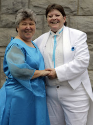 Dressed in their wedding attire, Kitty Lambert, left, and Cheryle Rudd, right, pose for a photo for a newspaper photographer before their wedding in Niagara Falls, N.Y., Saturday, July 23, 2011. The Buffalo couple wants Mayor Paul Dyster to pronounce them married one second after midnight _ the moment the law takes effect and makes New York the sixth and largest state to sanction gay marriage. (AP Photo/David Duprey)