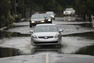 Cars cross flooded street, Thursday, Sept. 8, 2011, in the Manayunk neighborhood of Philadelphia. Widespread flooding brought on by the remnants of Tropical Storm Lee was being blamed for two deaths in Pennsylvania, where inundated communities were evacuated and state offices closed down on Thursday because of the rising waters. (AP Photo/Matt Rourke)