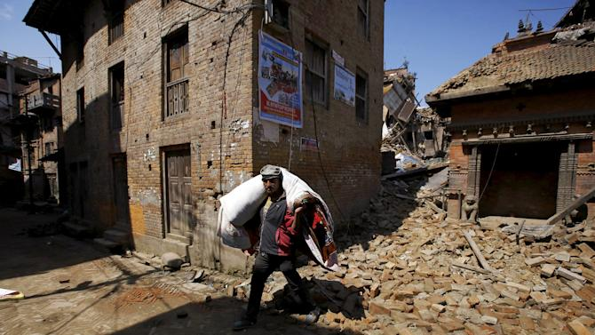 Man carrying bedding walks past rubble of collapsed houses following Saturday's earthquake in Bhaktapur, Nepal