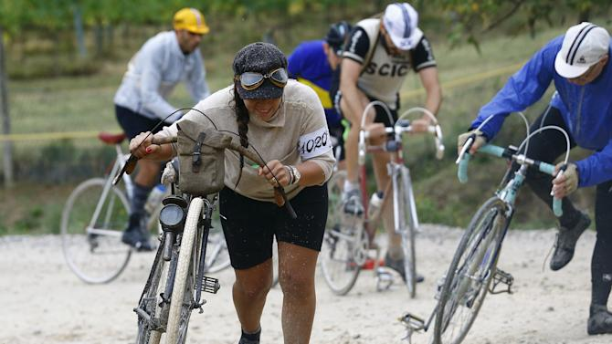 "Cyclist pushes her vintage bicycle on gravel roads during the Strade Bianche section of the ""Eroica"" cycling race for old bikes in Gaiole in Chianti"