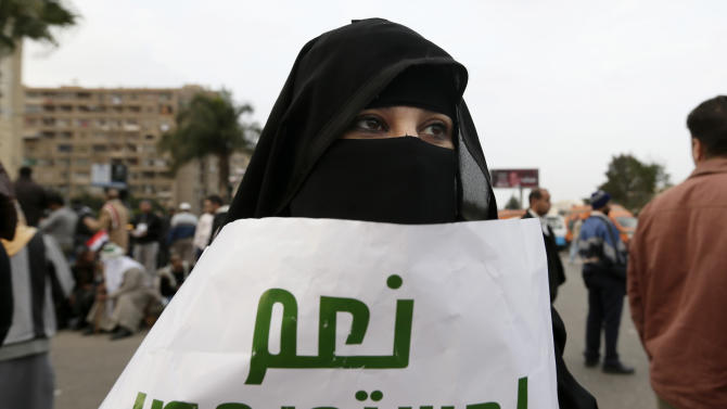 """A supporter of Egyptian President Mohammed Morsi attends a rally in Cairo, Egypt, Friday, Dec. 14, 2012. Arabic on the poster at center reads, """"yes to the Egyptian constitution."""" Muslim clerics urged worshippers to vote """"yes,"""" while thousands of supporters and opponents of a controversial draft constitution filled the streets of Cairo on Friday in dueling protests on the eve of a referendum on the charter that has left the country deeply polarized. (AP Photo/Hassan Ammar)"""