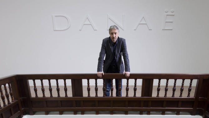 In this photo taken on Tuesday, May 28, 2013 artist Vadim Zakharov poses with his installation 'Danae' in the Russian Pavilion during a press preview of the 55th edition of the Venice Biennale of Arts in Venice, northern Italy. (AP Photo/Domenico Stinellis)