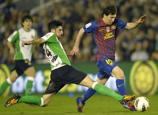 FC Barcelona's Argentinian forward Lionel Messi (R) controls the ball next to Racing Santander's Alvaro Gonzalez (L) during the Spanish league football match Racing vs Barcelona, at El Sardinero Stadium in Santander. Barcelona won the match 2-0.