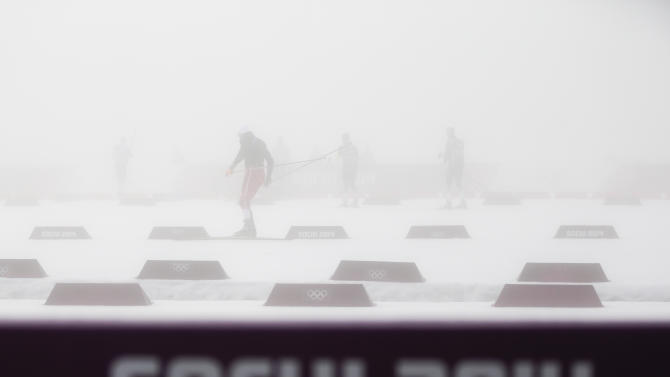 Athletes warm up in thick fog prior to the men's biathlon 15k mass start, at the 2014 Winter Olympics, Monday, Feb. 17, 2014, in Krasnaya Polyana, Russia. The men's 15-kilometer mass-start biathlon race at the Sochi Olympics has been delayed for an indefinite time due to fog, one day after the event had been called off for the same reason. (AP Photo/Gero Breloer)