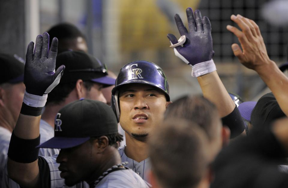 Colorado Rockies' Carlos Gonzalez is congratulated by teammates after hitting a solo home run during the first inning of their baseball game against the Los Angeles Dodgers, Friday, Aug. 26, 2011, in Los Angeles. (AP Photo/Mark J. Terrill)